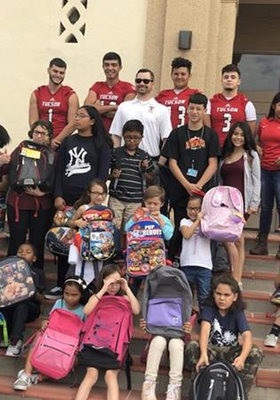 The football team distributes backpacks it collected to TUSD students in need.
