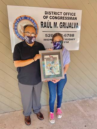 Ms. Blair holds her art with Rep. Grijalva in front of a sign for his Congressional District Office