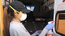 Photo of Woman in Mask Cleaning Bus Window