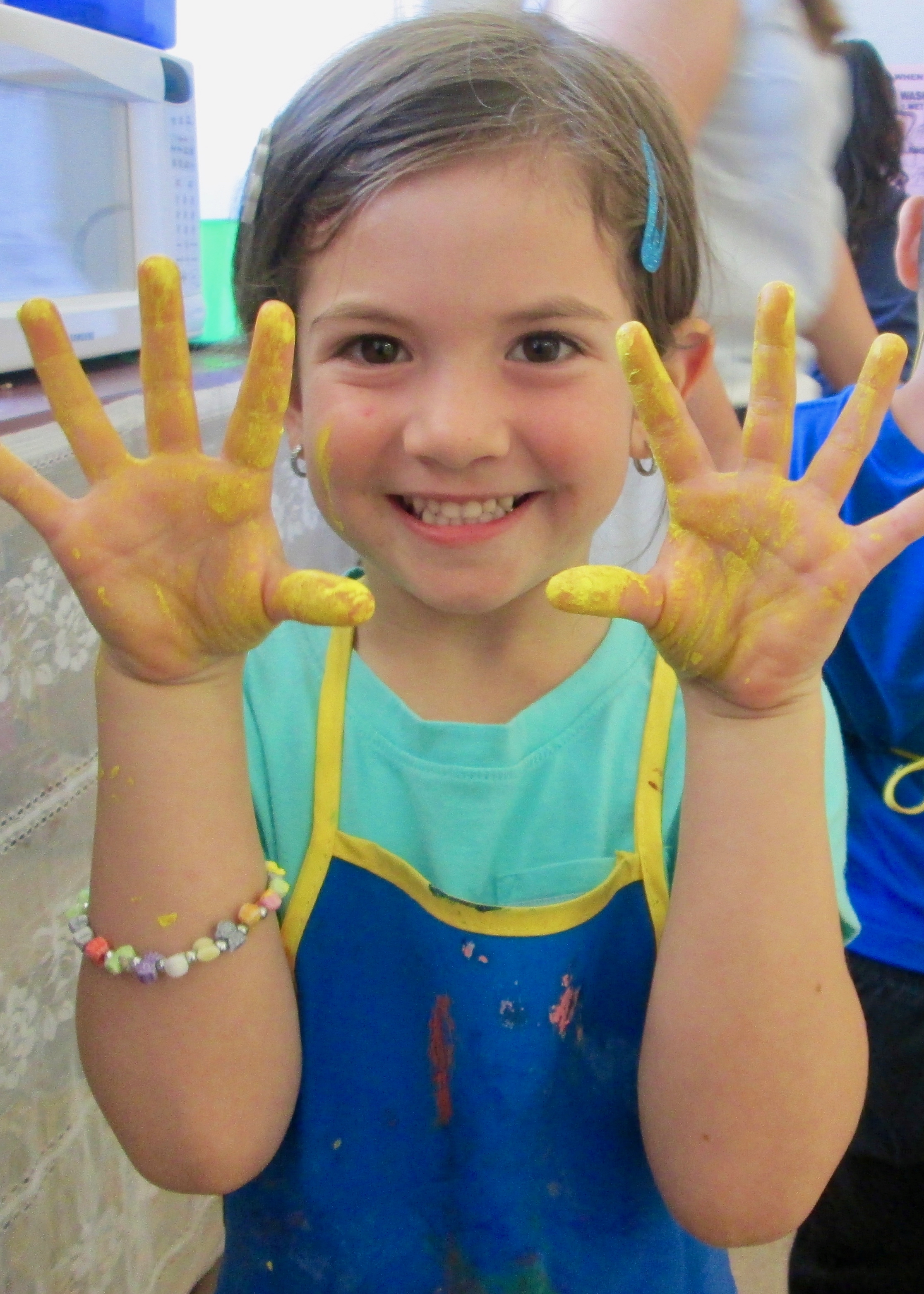 Girl with yellow painted hands.