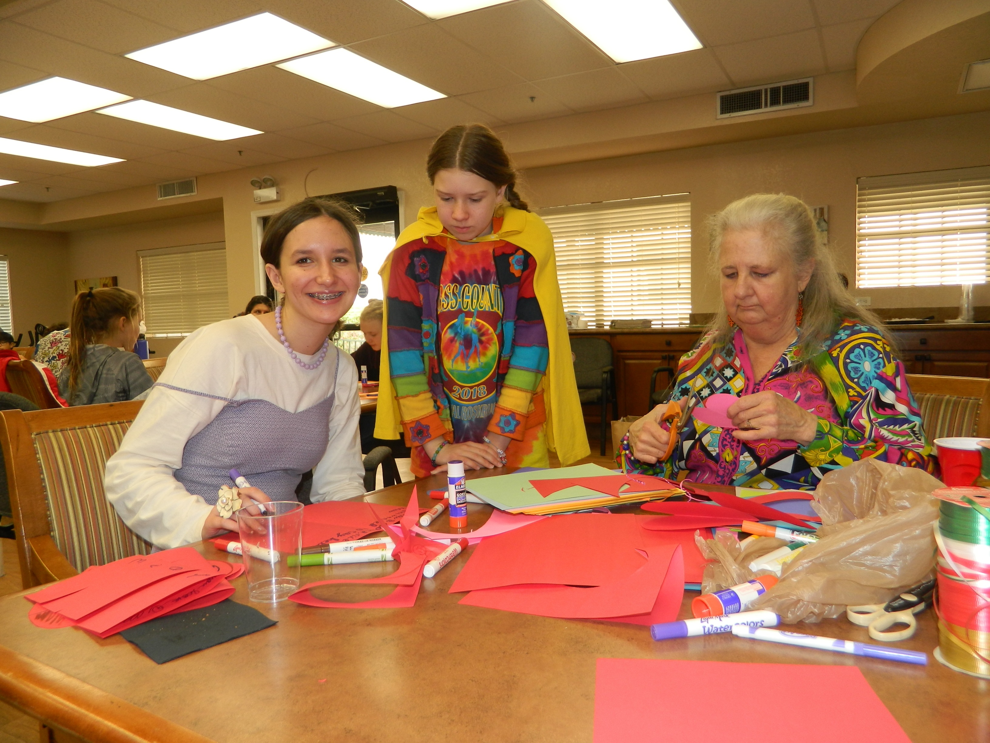 Teacher sitting with two students making cards for the elderly