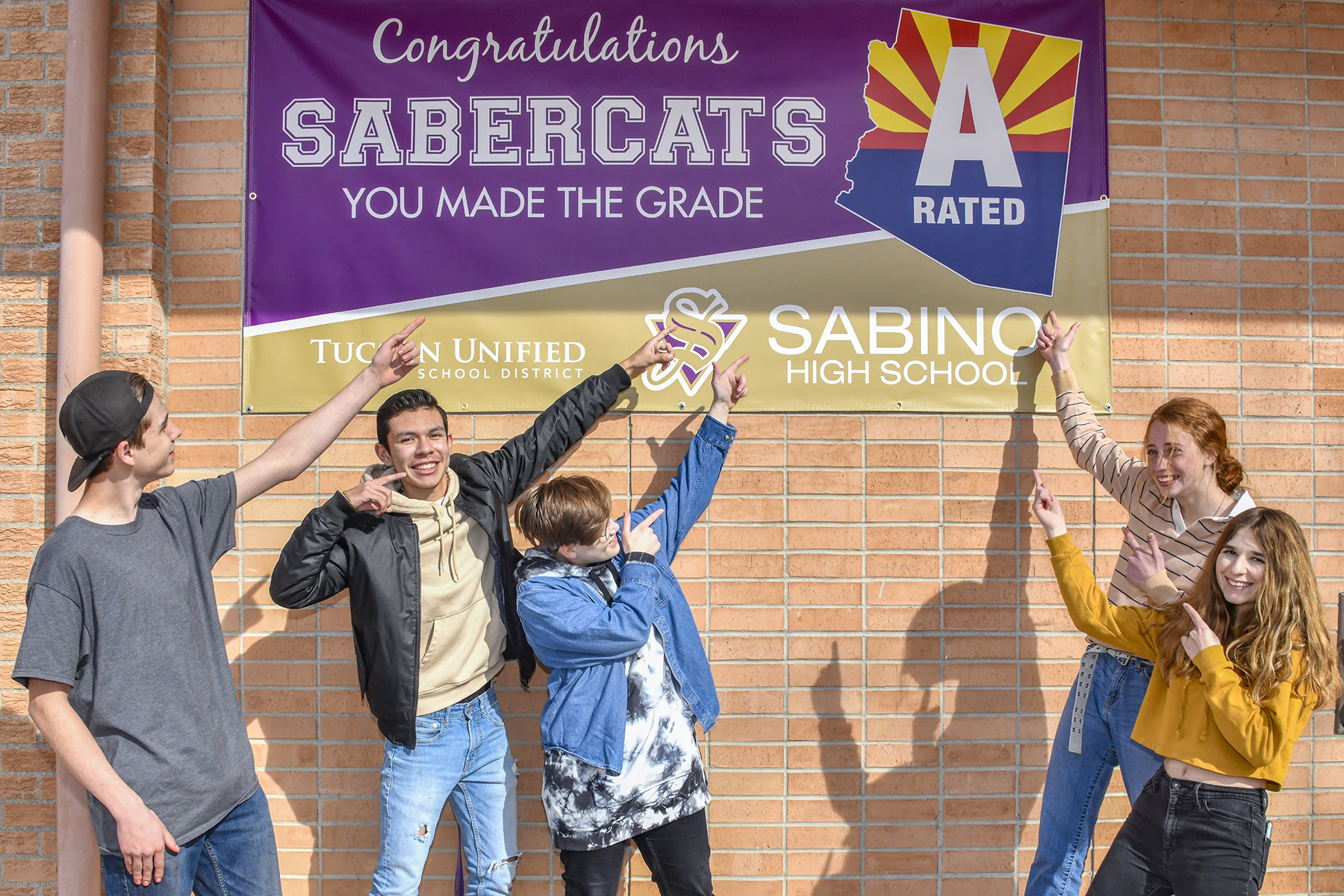 Students Pointing to new Sabino A school Banner