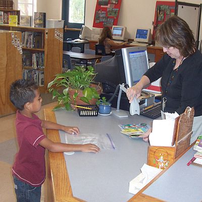 Librarian checking book out for boy