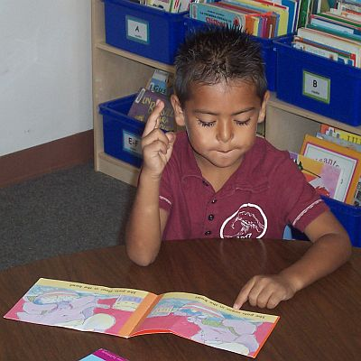 Boy holding up two fingers while reading a book