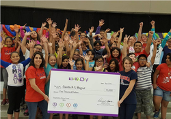 students and teachers holding large check