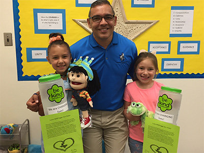 Marshall Principal Christopher Loya poses with two students and change jars for their change drive.