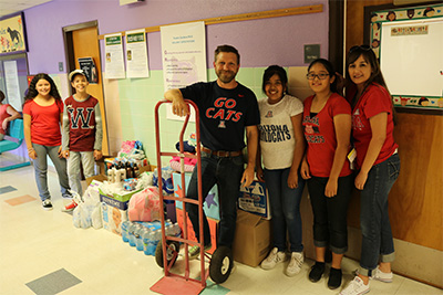 Students and staff from Pueblo Gardens pose by their donation pile.