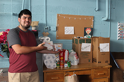 A Pueblo student with donations from their drive.