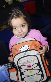 Preschool student holding backpack