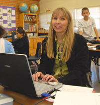 Image of teacher and student using laptops