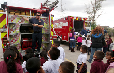 Fireman standing on back of firetruck talking to gathered children about fire safety